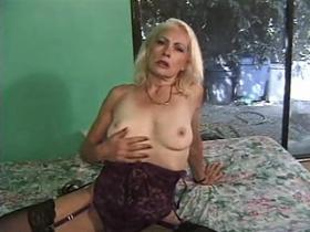 Nice blonde granny in black stockings teases her pussy